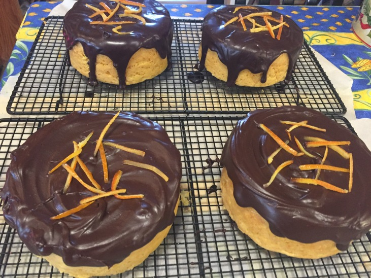 Orange cakes with dark chocolate ganache and candied orange peel.